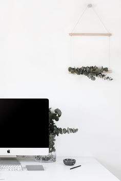 karien anne - minimal workspace / study space - iMac on a white desk with a branche hanger on the wall