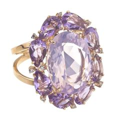 18K Rose Gold Amethyst Madame Ring : You can practically smell the sweet scent of lilac when you wear this Amethyst cocktail ring from Brazilian designer VIANNA's Madame collection, featuring a light purple, lilac-hued Amethyst surrounded by deeper, darker purple Amethysts set in rich 18k rose Gold. The country's native gemstones command center stage in this collection, and the precious rose Gold gives a touch of old-fashioned romance to this statement piece. •$1,950.00