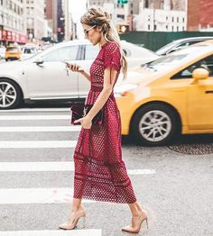 Christine Andrew of Hello Fashion wears a lace midi dress, Saint Laurent clutch, and nude pumps