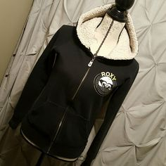 Roxy Surf hoodie Roxy hoodie jacket, with working zipper, decorative buttons down the side, shark emblem on the back, fur lined hood, one small area in the sleeve that the stitching came out. Comes from a smoke free home Roxy Tops Sweatshirts & Hoodies