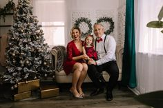holiday mini session photo shoot christmas family neutral greenery garland tree lights screen sofa couch hugging red black dress tux suit suspenders bow tie
