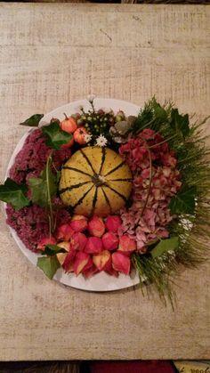 Groot bord, ring osasis. Bloemen (sedum, hortensia, herfstaster, conifeer en klimop uit eigen tuin), nep spulletjes en in het midden een grote kalebas