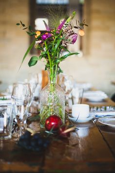 A stunning winter wedding table with deep purples and reds in the form of fruit and flowers, styled by Glass Slipper Weddings