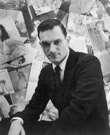 """Portrait of American publisher Hugh Hefner sitting in front of a wall collage of female centerfolds from his men's magazine """"Playboy"""" which he launched in 1953."""