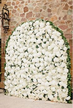 Arched Flower Wall with White Hydrangeas. Dress up a stone wall by creating an elegant, arched flower wall for the ceremony filled with fluffy white hydrangeas. Created by Roni Fleurs.