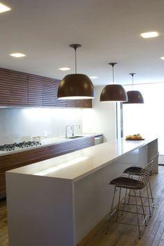 """plafon para iluminação geral embutidos no forro e luminária """"tipo bossa"""" pendente sobre balcão"""