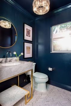 Navy walls make this powder room shine. Gold and marble vanity. Chevron tiles. Gold mirror and chrome faucets for a mixed metal look