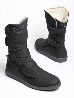 This season's release of the Margiela high top is a mid-calf paneled motorcycle boot with two adjustable Velcro straps on the outer side and a Velcro fastening front panel. The sole is the same as the classic Margiela army replica sneakers and is done in a vulcanized grey. Uppers come in black rubber, red leather …