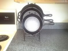 "DIY CAST IRON SKILLET COUNTER DISPLAY After looking everywhere for a graduated display rack for my cast iron skillets, my husband and I bought different sizes iron picture frame holders and they fit my 12"", 10"" and 8"" skillets perfectly.  Bed Bath & Beyond $33.00."