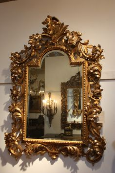 "Antique Italian wood carved gessoed and water gilt mirror in 24k gold circa 1800. Measurements are 38"" wide and 54"" tall."