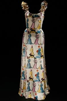 """Elsa Schiaparelli.  Two-Piece evening dresses, Bodice and Skirt Circa summer 1939.  Made from white silk satin with multicolored """"Mae West"""" figures."""