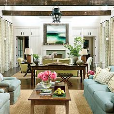 "The Living Room: Front and back doors open directly into a two-story-high living room, where spruce-planked walls and wood beams salvaged from an 1890 Tennessee barn reflect the home's rural setting and give the space a refined, barnlike feel. Interior decorator Phoebe Howard balanced the rustic elements with color. ""I added an air of elegance with a soft color palette that reflects the surrounding sky and hills,"" she says."