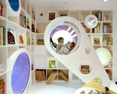 The Space Shuttle Reading Room, Beijing, China  --  Sako Architects realized this amazing project for Poplar Library, a bookstore specific for children. Main features of the projects are 2 rainbow colored ribbons floating around the 2 floors inviting children to discover the shop world made of spaces and holes to explore. Holes in the bookshelves can be passages for other rooms or little lairs to enjoy a book.