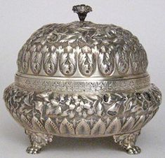 silver & gold, England, A sterling silver J.E. Caldwell butter dish, late 19th century with a domed lid and ovoid sides with foliate repousse decoration, raised on four paw feet.1880 - 1900