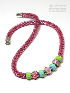 Magenta, Aqua and Lime Combo. Charming glass focal beads in combinations of magenta, aqua and lime are featured in this simple Kumihimo design. The hand-made focal beads with flowers and swirls, are by Grace Lampwork Beads. I braided magenta cylinder beads into sleek, flexible ropes on both sides of the focal beads. The necklace is finished with a silver-plated, magnetic clasp that locks. Kumihimo is an ancient Japanese braiding art, combining silk strands or other materials into elaborate…