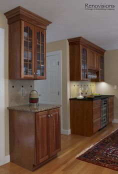Kitchen remodel by Renovisions. Decorative tan and black tile backsplash. Granite countertops and Natural Cherry cabinets with under cabinet lights and glass front cabinets. Bar area with beverage fridge.