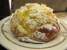"""One of my all-time favorite breakfast pastries is the puffy  pão de Deus (""""bread of God""""). It has to be good with a name like that. Barely sweet, made with milk  with a wonderful coconut topping dusted with powdered sugar, it's usually served cut into quarters."""