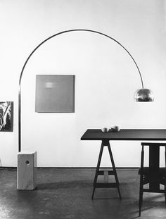 FLOS Arco by Achille and Pier Giacomo Castiglioni adds timeless style to this monochromatic modern dining room featuring contemporary wall art.