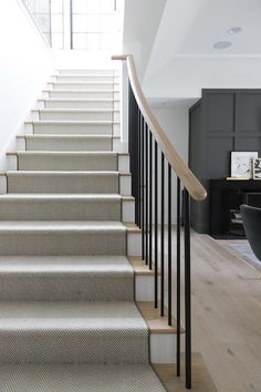 White and black herringbone staircase runner accents blond wood treads complemented with a blond wood handrail and iron spindles.