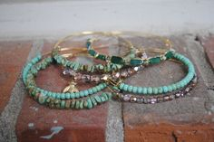 "All Adjustable Bangles are Handmade & Gold Plated .  2- Green & Brown Magnesite random trapezoid bangles 2- Green Magnesite round stone bangles  1- Emerald Aventurine & Gold Czech fire-polished glass bead bangle 1- Blush & Gold ""Queen Bee"" Bangle 1 Blush & Gold Czech fire-polished glass bead bangle.  bricksandbaubles.com"