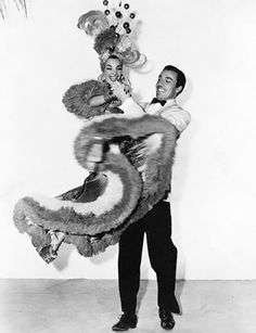 "Cesar Romero and Carmen Miranda    1941 - Monte Blanca (Cesar Romero) lifts Rosita Rivas (Carmen Miranda) into the air as they dance in a publicity still for ""Week-End in Havana""."