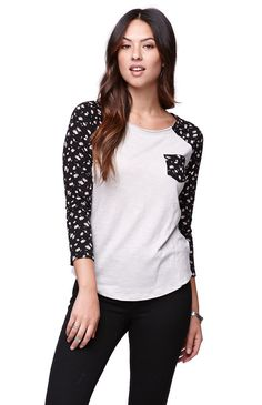 """We're stocking up on the3/4 Sleeve Fitted Raglan T-Shirt by Nollie thanks to its print throughout and laid back style. This t-shirt would look great with everything from our shorts to skinny jeans! The fabric is super light weight and we love the front pocket detail.25"""" length20"""" sleeve lengthMeasured from a size smallModel is wearing a smallHer measurements: Height: 5'7"""" Bust: 32"""" Waist: 24"""" Hips: 34""""60% cotton, 40% modalMachine washableImported"""