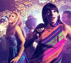 People dancing in disco. Purple dress. London, 60s.