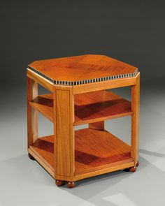 PAUL FOLLOT (1877-1941). A mahogany and rosewood veneer coffee table with three superimposed tops adorned with fine ebony lines and bordered in ivory elements. Circa 1925.