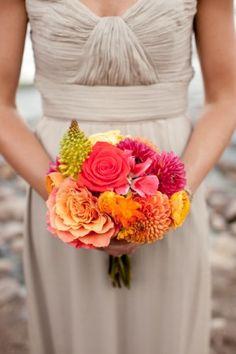 Muted wedding party colors offset brightly colored wedding flowers and decor.