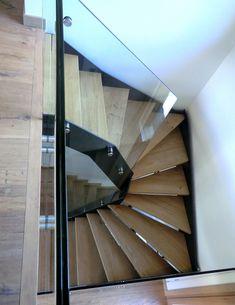 Escalier Loft avec limons acier thermo laqué, garde-corps tout verre et marches en chêne sablées.