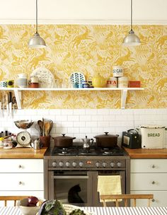 Harvest interiors themed kitchen with metro tiles, yellow wallpaper and stove