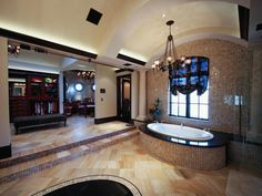 This opulent master bathroom is attached to the master suite in this million dollar home in Hidden Hills, Calif. A spa tub stuns in the center of the bathroom, while steps lead up to a luxurious dressing room on the left side of the room.