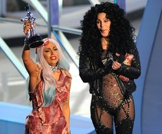 Lady Gaga raises her Moonman next to Cher while wearing a meat dress at the 2010 Video Music Awards.