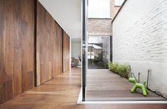 De vloer in Amerikaanse notelaar loopt door in de lange kastenwand en contrasteert met de witte muur die het licht via de patio naar binnen zuigt.