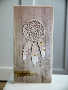 handmade card from Blütenstempel ... tall and thin format .. weathered wood look on backgrund ... die cut dream catcher with three grunge splatted die cut feathers ...