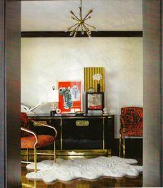 black and brass dresser, sheep shkin rug, black mouldings, brass chandelier