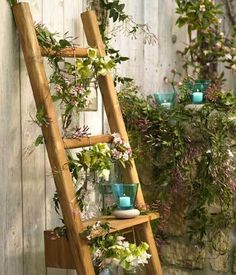 Ladders hold a special fancy in my heart. I  can't help but feel even the most rugged of ladders has a bit of romantic whimsy in them. Every great romance has a moment involving a ladder -- at least they should. No other single object can promise to both ascension to great romance and a fall into a love even deeper. Perhaps I wax poetic, but with a vision like this ladder can you hardly blame me! Complete with wrapping flowering vines, candles, and dangling blossoms in Mason Jars of water…