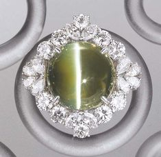 A CAT'S EYE CHRYSOBERYL AND DIAMOND OBI CLASP    The cat's eye chrysoberyl weighing 50.71 carats within a vari-cut diamond surround, mounted in platinum, 3.2 cm wide