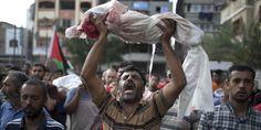 Un hombre levanta el cuerpo de un niño, de 1 año, muerto el jueves en el ataque a una escuela de la ONU en Gaza. / MAHMUD HAMS(AFP)