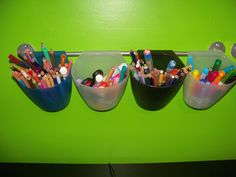 Storage idea for kids art supplies :   Containers and rod were purchased from IKEA's kitchen section.  These were mounted above a desk holding markers, colored pencils, scissors, etc.  The cups come right off and sit upright on any flat surface.