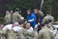 Pass it on: Princes William and Harry joined soldiers who were transferring sandbags at Eton End school in Datchet