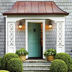 Turquoise front door framed with white columns and a copper roof. Very inviting.