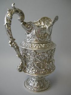 This magnificent sterling silver pitcher was made by the Gorham Mfg. Co. of Providence, RI in 1893. It is fully hallmarked with Gorham's maker's mark, style # 5128 and date mark for 1893. The pitcher is of majestic proportions and is finely cast, chased, repousse and engraved with a maskhead spout, and a mid-section with gryphon, putti and Bacchanalian scenes. The handle is cast and chased with floral, acanthus leaf and scroll motifs. The pitcher is raised on an acanthus leaf-capped…