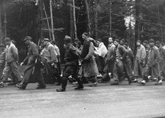 Prisoners on a death march from Dachau move towards the south along the Noerdliche Muenchner Street in Gruenwald, Germany, on April 29, 1945. Many thousands of prisoners were marched forcibly from outlying prison camps to camps deeper inside Germany as Allied forces closed in. Thousands died along the way, anyone unable to keep up was executed on the spot.