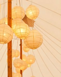 Groupings of glowing lanterns hang from a tent's center pole