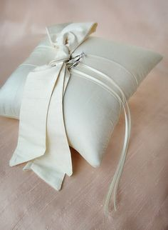 The love knot ring pillow is in a world all its own. Simple and different, it is great for a wide range of weddings. Off center silk sash bows come together with a dupioni silk base pillow where the rings tie onto the center of the pillow bringing balance to the design.Sorry, rings shown are not included.Available in white or ivory. Shown here in ivory.Measures about 8 inches square or about 20 centimeters square.Features thin satin ribbons to attach your rings and a...