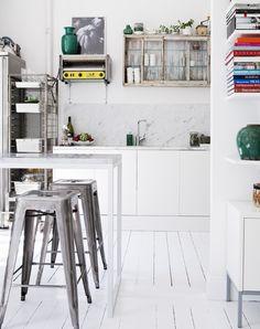 Vitt, rostfritt och marmor i köket. Sittdelen i förgrunden, Tolixpallar och högt barbord med marmorskiva. Foto: Andrea Turander