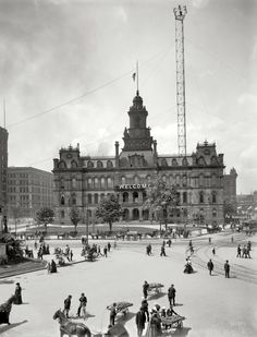 "Detroit, Michigan, circa 1900. City Hall and Campus Martius. To the left, the Soldiers and Sailors Monument; rising to the right is one of the city's ""moonlight tower"" carbon-arc lamps. Palm trees and bananas strike a tropical note."
