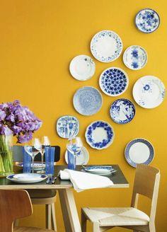 Het koele blauw tempert de vrolijk gele wand, het koud-warm contrast brengt balans.