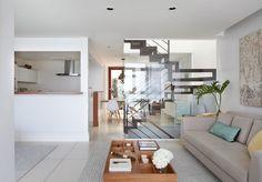 Apartamento, decoração de apartamento, com tons neutros. Sofá, cadeira de madeira, mesa de centro de madeira e adornos.